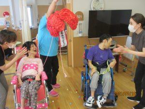 車椅子に乗った二人の利用者さんの間に赤いくす玉が割れて飾りが出ている様子