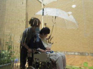 利用者さんとスタッフがビニル傘をさして雨を感じている様子