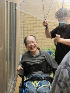 雨の中、透明のビニル傘を男性の利用者さんにさしてあげている様子