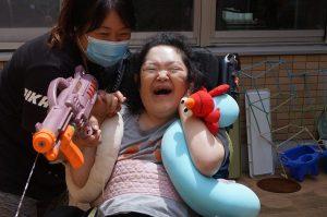 スタッフと一緒に水鉄砲を抱えて満面の笑顔の女性の利用者さんの様子