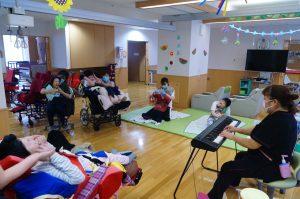 デイルームに集まっている利用者さんの様子 車椅子に座っている方、床に座っている方などがいる様子