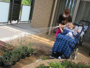 テラスで、千日紅の花にむけてスタッフと車椅子に座った利用者さんがお水をまいている様子