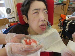 車椅子に乗った利用者さんにイチゴ味のかき氷を差し出している様子