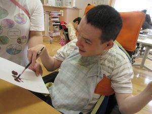 車椅子に乗った男性の利用者さんが筆で紫色のぶどうを書いている様子