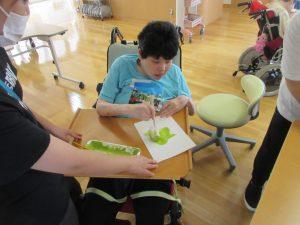 車椅子に乗った女性の利用者さんが黄緑色のぶどうを筆で書いている様子