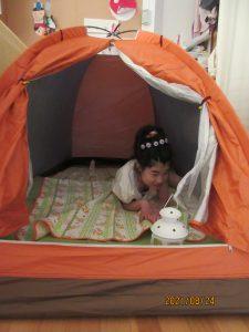 オレンジのテントの中に女児の利用者さんが寝そべっている様子