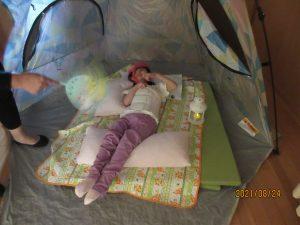 青のテントの中に別の女児の利用者さんが寝そべっている様子