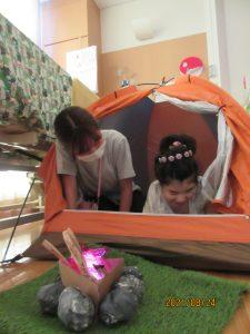 オレンジ色のテントに女児の利用者さんとスタッフが楽しそうに入っている様子