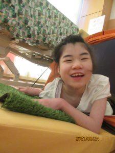 テントの中で寝そべっている笑顔の女児の利用者さん