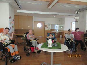 車椅子に乗った利用者さんが5人、デイルームに集まっている様子