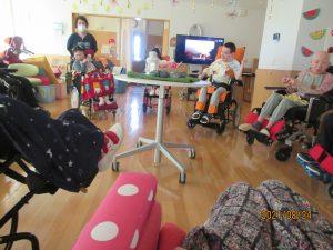 車椅子に乗った利用者さんやスタッフが数人集まって歌を歌っている様子