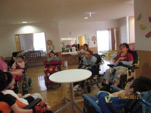 薄暗くしたデイルームに数人の車椅子に乗った利用者さんが集まっている様子