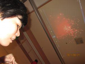 女性の利用者さんの上にある天井に赤い花火の影像が映し出されている様子