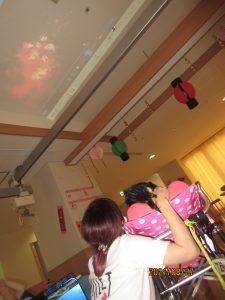 天井に赤く映し出されている花火の影像をスタッフと利用者さんが上を眺めている様子