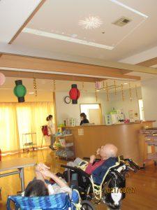 車椅子に乗った二人の利用者さんが、天井に映し出されている花火の影像を上を向いて眺めている様子
