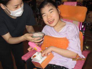 笑顔の女児の利用者さんがスタッフからかき氷を差し出されている様子
