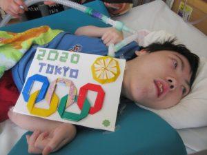 横井になった利用者さんと手作りのオリンピックマークと一緒に写った写真