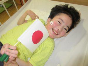 別の女性の利用者さんが手作りの国旗を持って笑顔で横たわっている様子