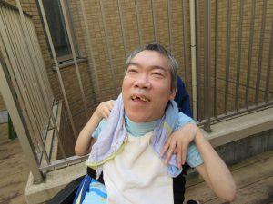 テラスで男性の利用者さんが首にタオルを巻いて笑顔でみえる様子