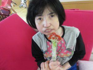 女性の利用者さんが赤い千日紅のブーケを持っている様子