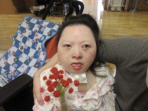 別の女性の利用者さんがたくさんの赤い千日紅の花のブーケを持っている様子
