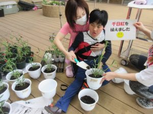 女性スタッフと一緒に女性の利用者さんが一緒に手を支え合いながら、スコップで植木鉢に土を入れている様子