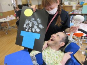 お月見の色紙と一緒に写る笑顔の男性の利用者さん