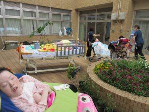 中庭の花壇に、車イスやベッドに乗った利用者さんとスタッフがいる様子