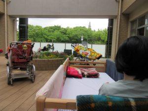中庭から外の公園の緑が見える場所で、3人の利用者さんが車イスやベッドに乗っている様子