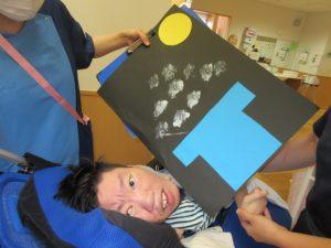 お月見のお団子が色紙で形作られているものと一緒に写る利用者さん