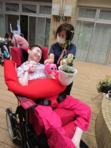 車イスに乗った利用者さんがピンクの動物の形をしたじょうろを持って、女性スタッフと苗に水やりをしている様子
