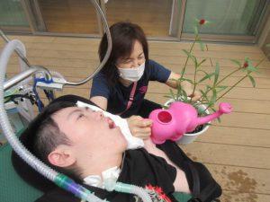 女性スタッフが呼吸器をつけた利用者さんの手を支えてピンクのじょうろを持ち、千日紅の苗に水やりをしている様子