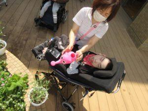 女性スタッフが車イスの利用者さんと一緒にピンクのじょうろを使って水やりをしている様子